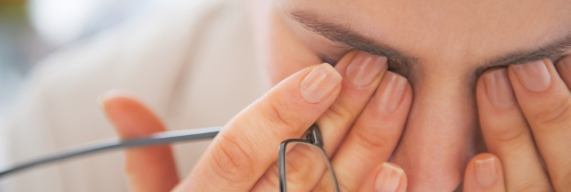 Picture of a woman fighting an eye fatigue.