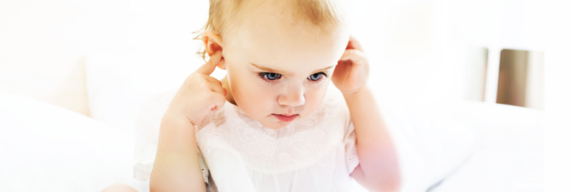 Picture of a baby girl covering her two ears in a white background.