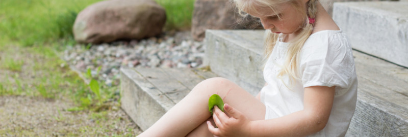 Picture of little girl covering her wounds with a green leaf in her leg.