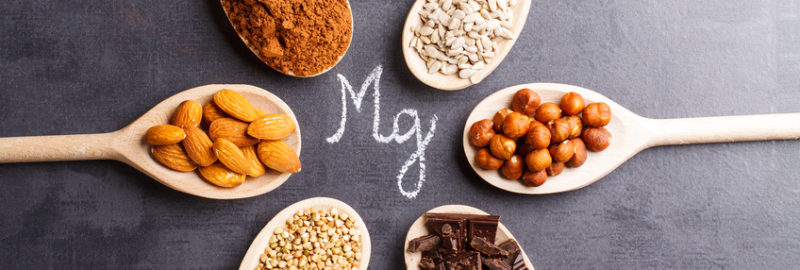 Picture of various foods high in magnesium like almond, chocolate, peanuts, watermelon seeds place in a wooden spoon
