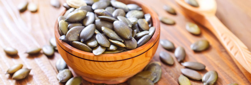 Picture of pumpkin seeds in a bowl place in a wooden table