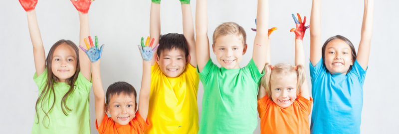 Six happy children wearing multiple colors raising their arms with their hands painted