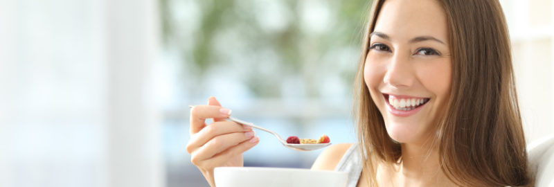 Beautiful and smiling girl eating cereals