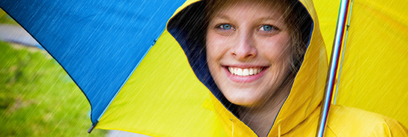 Happy woman in a yellow raincoat and umbrella.