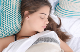 Picture of a pretty young woman sleeping in bed .