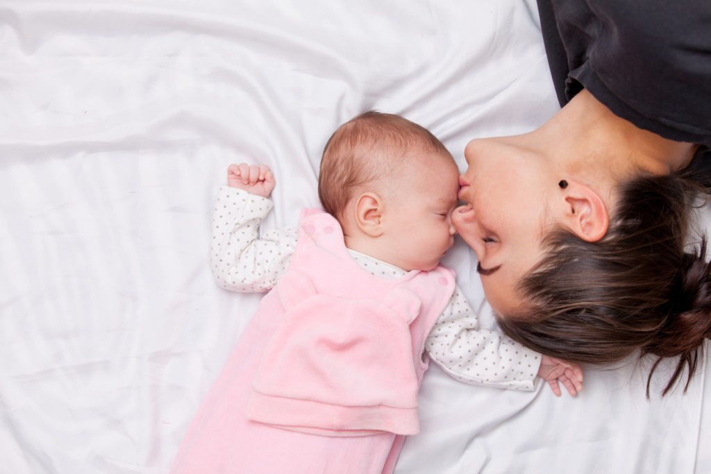 Mother kissing the forehead of her little baby in the bed.