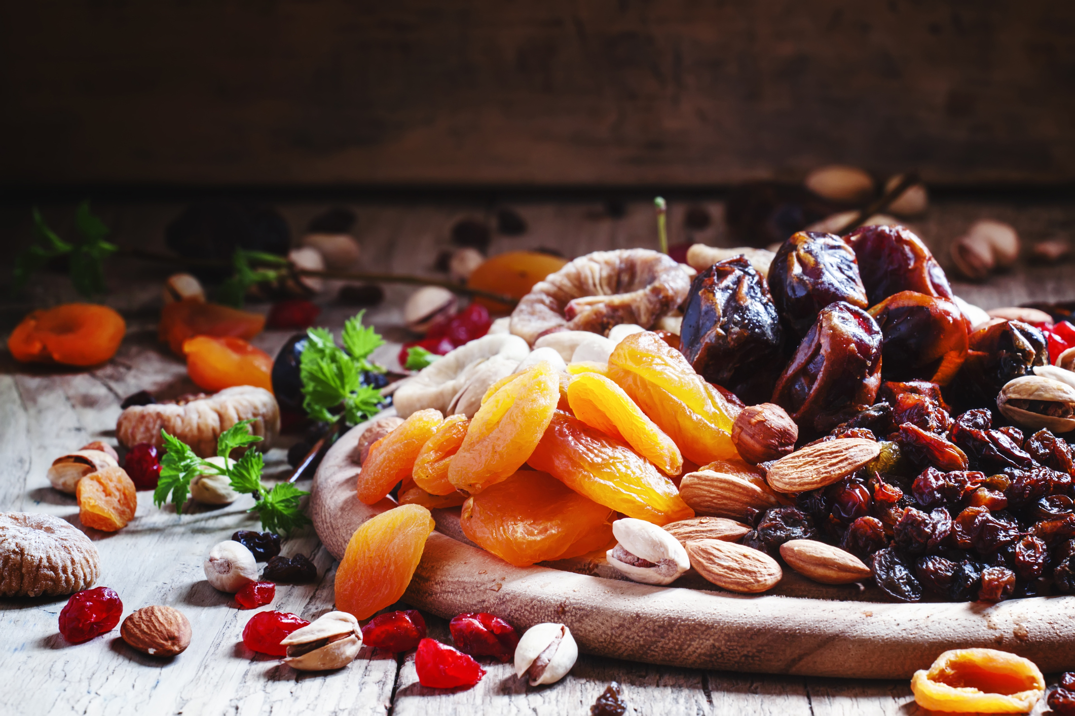 Dried apricots, dates, raisins and various nuts, vintage wooden background in a selective focus