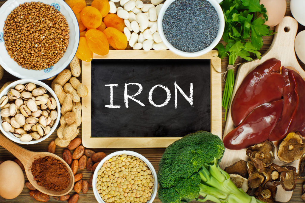 Collection of iron rich foods such as liver, buckwheat, eggs, parsley leaves, dried apricots, cocoa, lentil, bean, blue poppy seed, broccoli, dried mushrooms, peanuts and pistachios on wooden table.