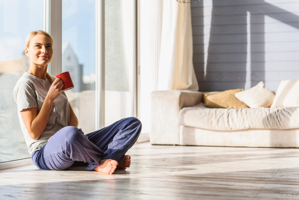 Joyful young girl is relaxing at home while sitting near window and drinking coffee.