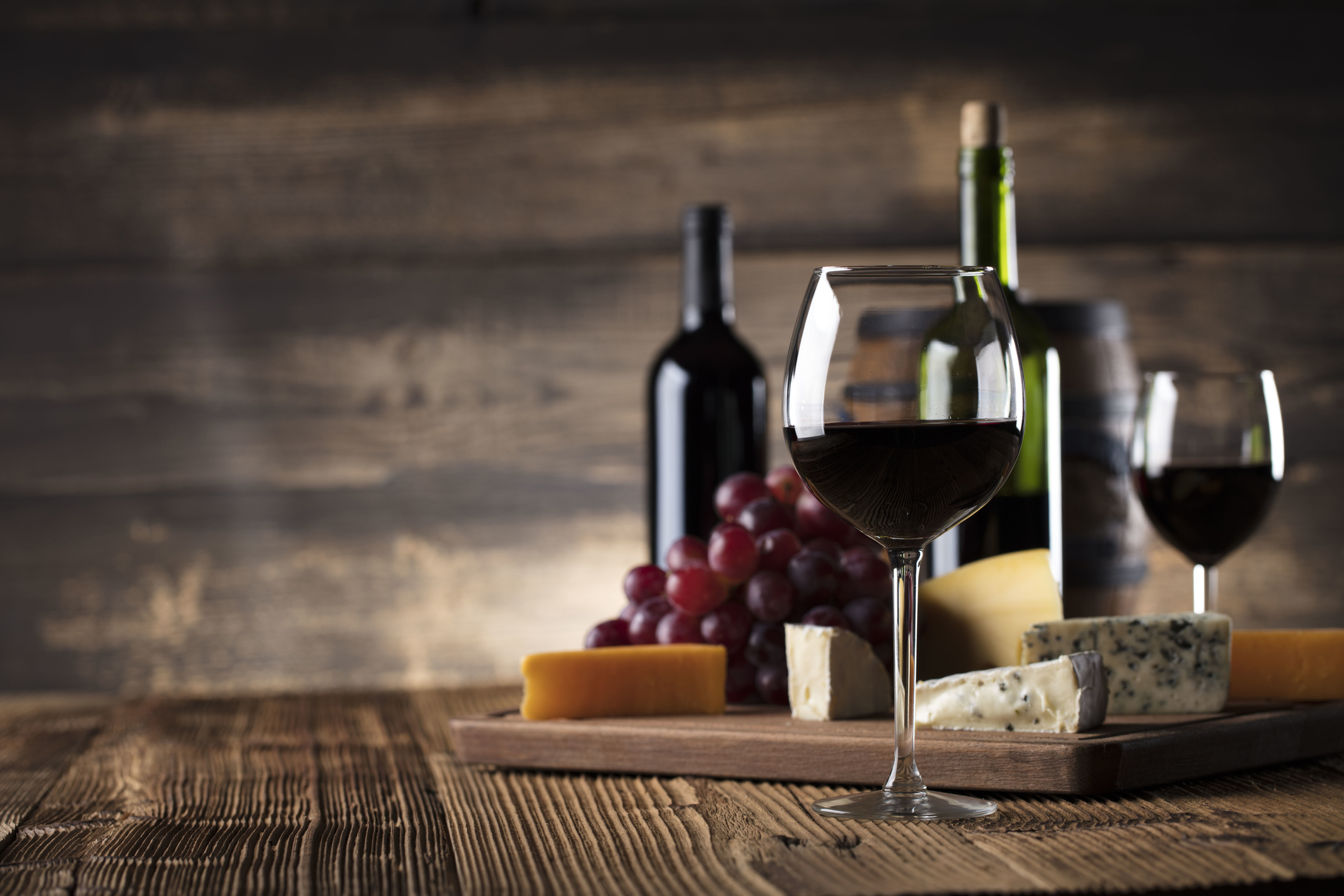 Red wine with cheese and grapes with a rustic background