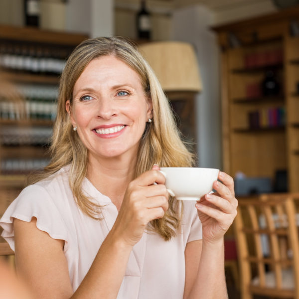 Smiling mature woman holding coffee cup and talking with her friend.
