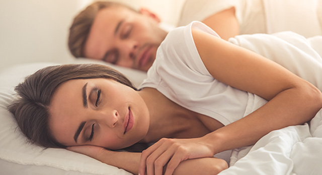 Young beautiful couple sleeping in bed with closed eyes.