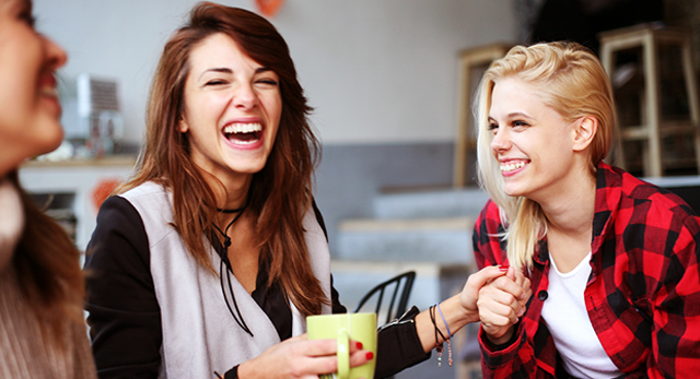 Happy smiling girlfriends with a cups of coffee.