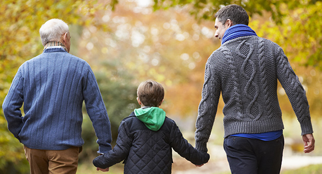 Picture of a Grand dad, Son and grandson holding hands while walking outdoors