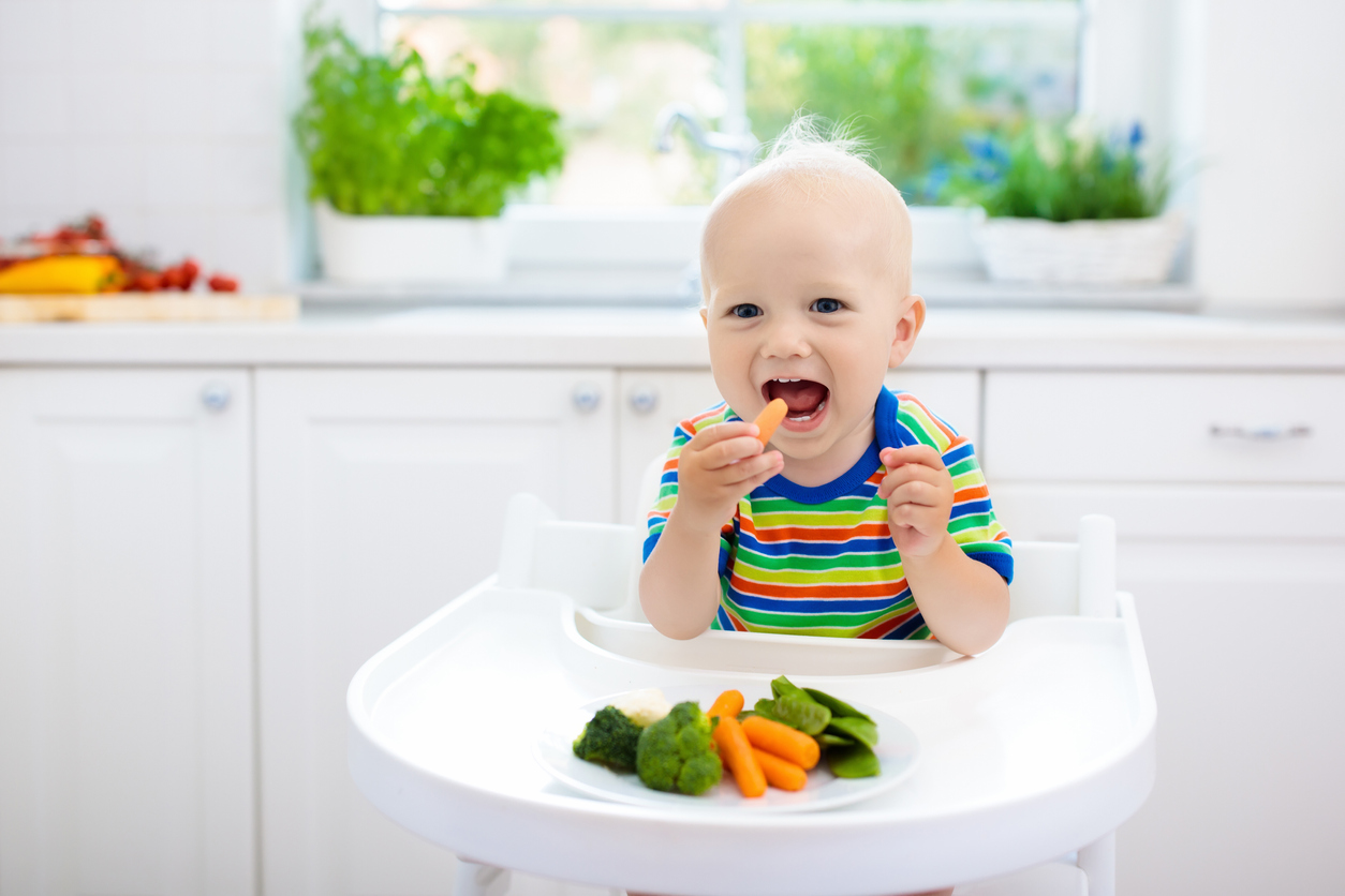 Cute baby eating a solid food, organic broccoli, cauliflower, carrot and green peas. in white kitchen.