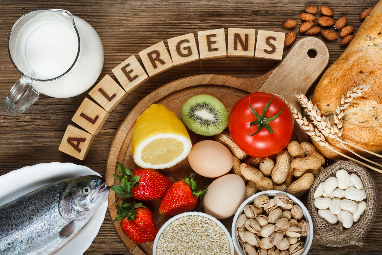 Allergen foods such as almonds, milk, pistachios, tomato, lemon, kiwi, trout, strawberry, bread, sesame seeds, eggs, peanuts and bean on a wooden plate.
