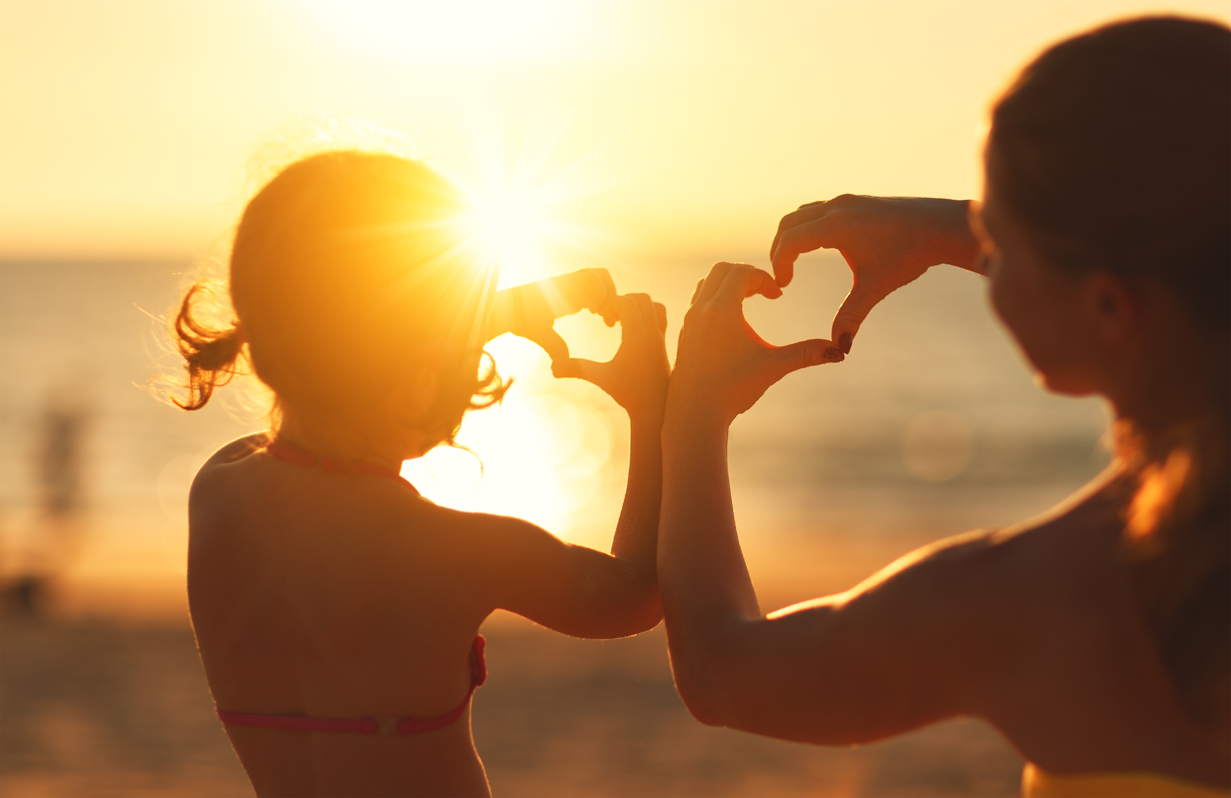Mother and child daughter show heart from hands at sunset on beach.
