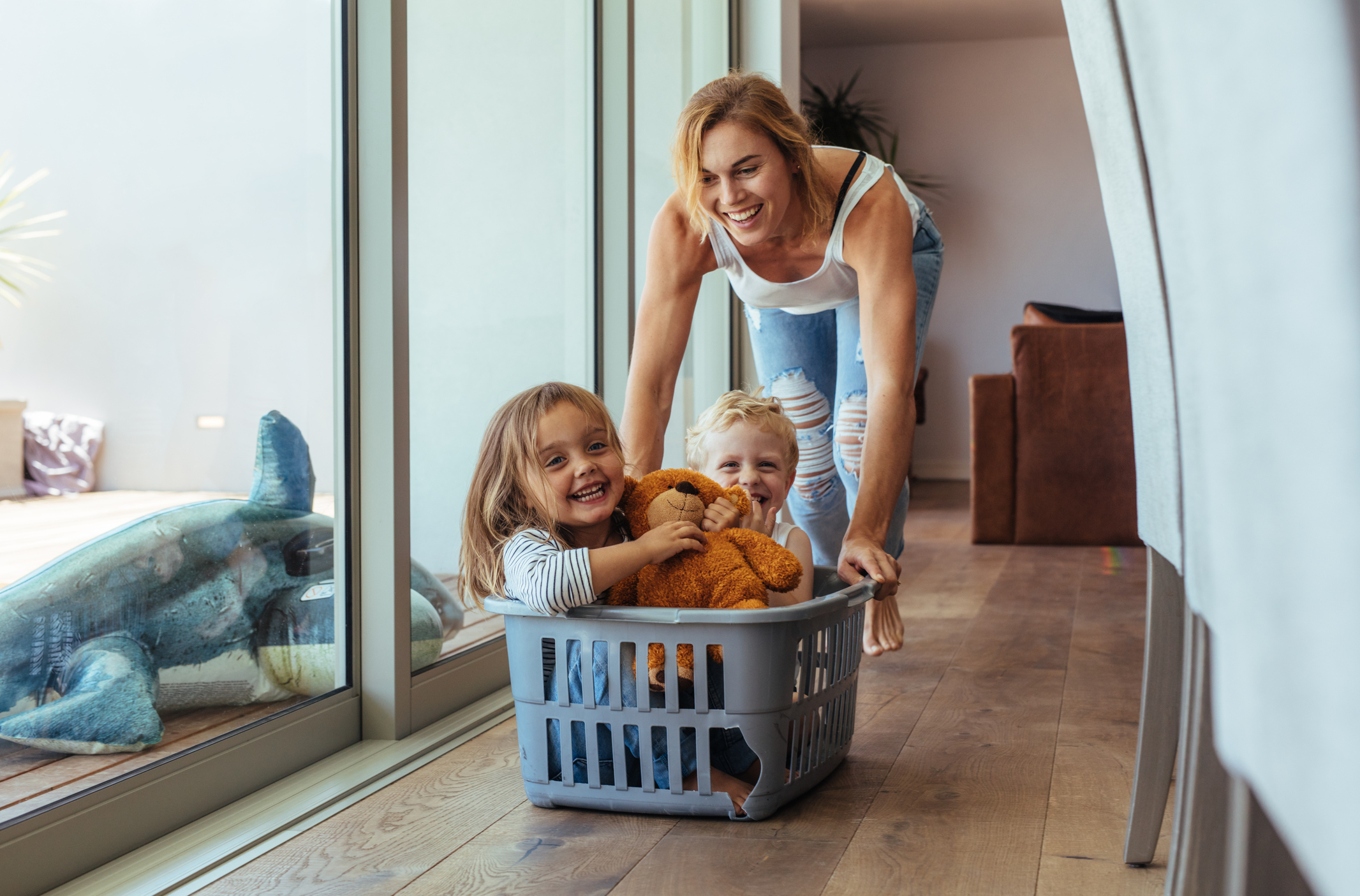 Happy young mother pushing her 2 children sitting in laundry basket at home